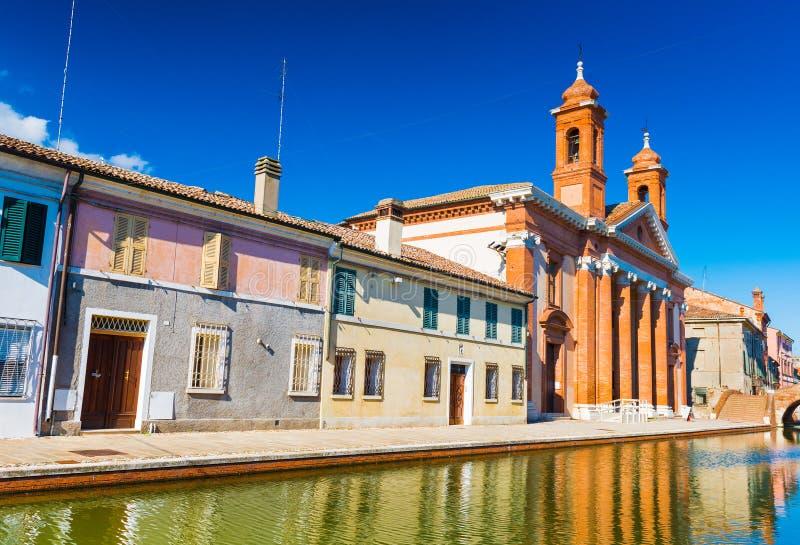 Sikt av gatan med kanalen och färgade hus, Italien arkivbilder