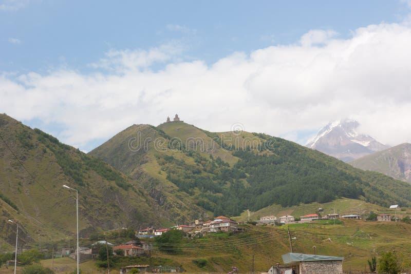 Sikt av Gergeti och Stepantsminda städer och Tsminda Sameba Kyrka för helig Treenighet nära Kazbegien royaltyfria foton