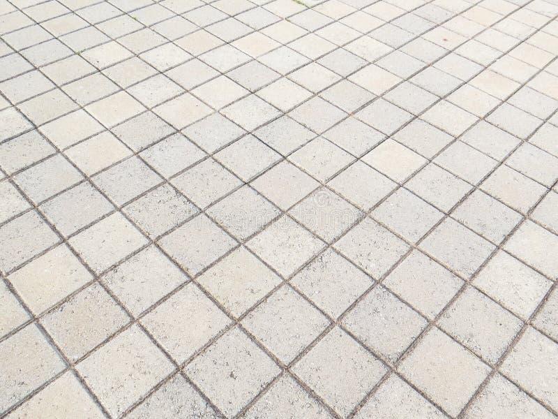 Sikt av golvet i fyrkantiga kvarter av cement på diagonalen arkivbilder