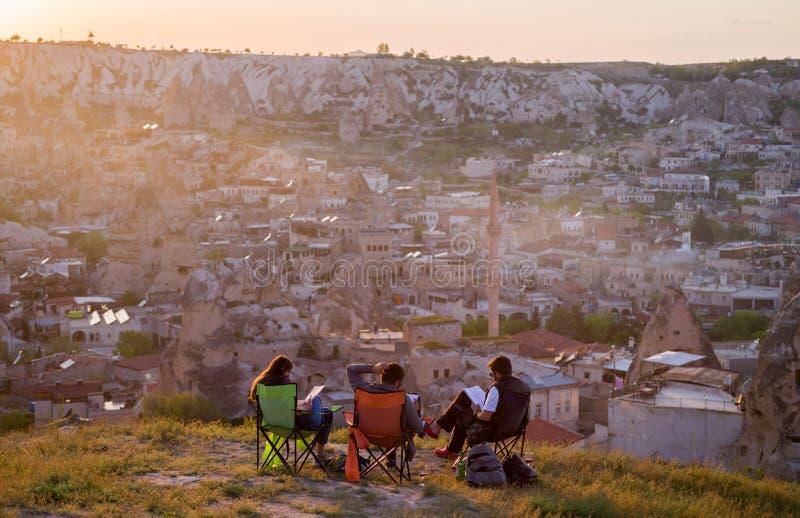 Sikt av Goreme på solnedgången med företaget av studenter i förgrunden, sikt från baksidan Cappadocia Turkiet royaltyfri foto