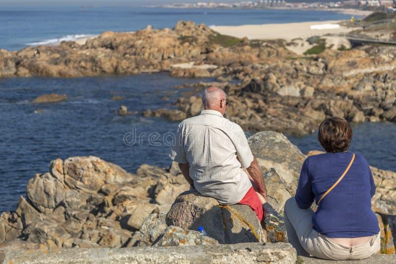 Sikt av höga par som kopplar av med sikt till den Leca da Palmeira stranden royaltyfri foto