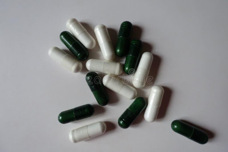 Sikt av högen av vita kapslar av magnesiumcitrate och gröna kapslar av multivatamins från över arkivbilder
