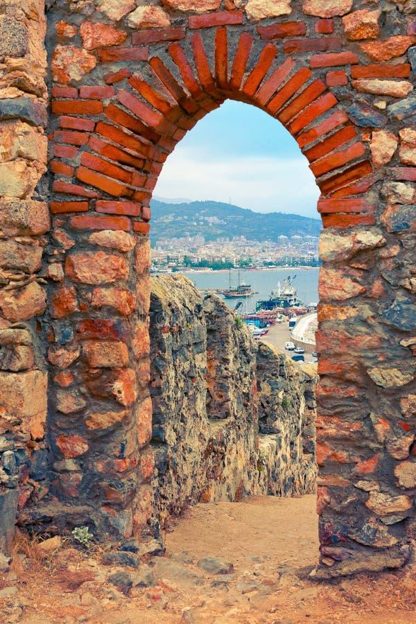 Sikt av hamnen till och med stenbåge av den Alanya slotten fotografering för bildbyråer