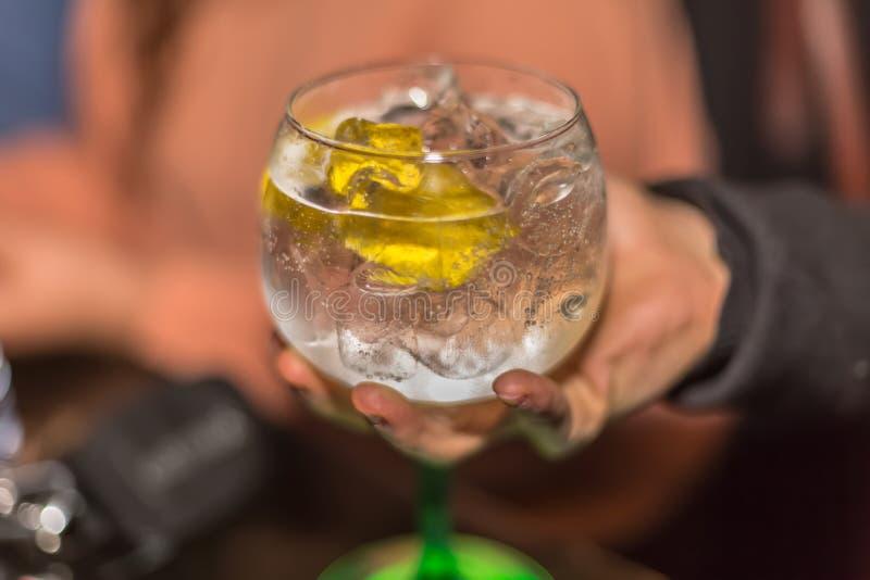 Sikt av handen som upp väljer ett exponeringsglas av förnyande gin, med citronen och massor av is, klassiskt exponeringsglas fotografering för bildbyråer