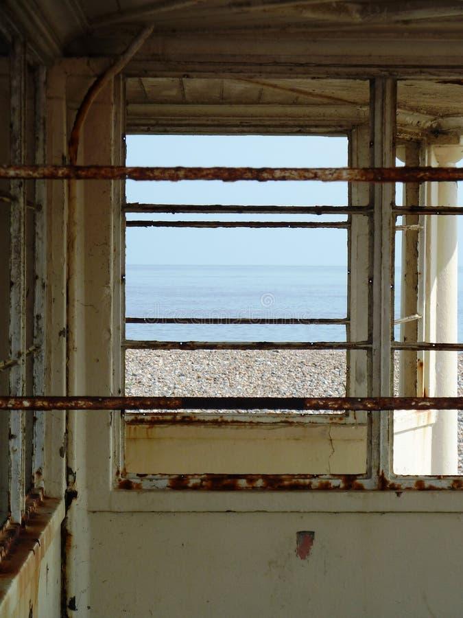 Sikt av havet till och med ett rostigt övergett strandskydd fotografering för bildbyråer