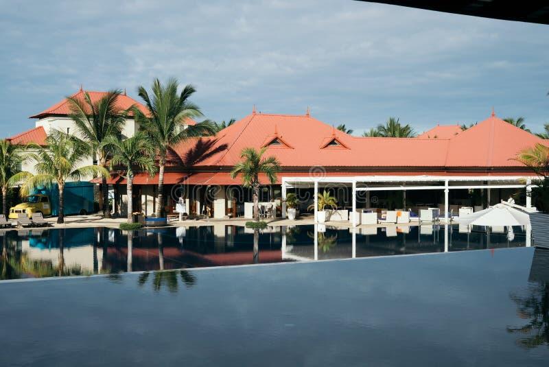 Sikt av hotellpölen med palmträd och vardagsrumsängar royaltyfri bild