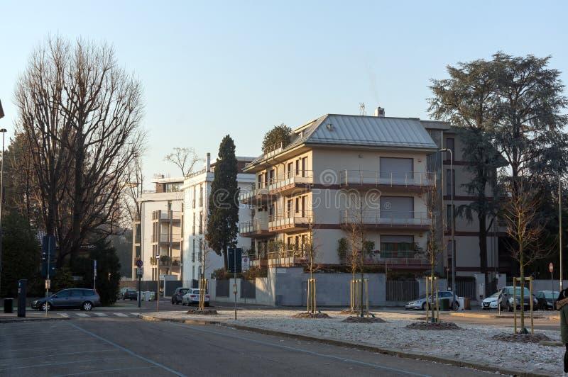 Sikt av hyreshusar med bilar på vägen i bostadsområdet av San Siro, i Milan, tidigt på morgonen arkivbilder