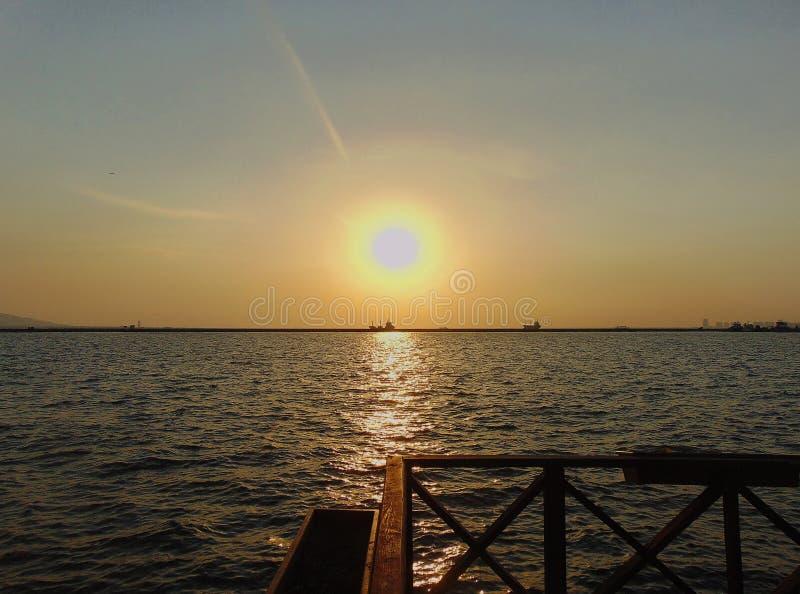 Sikt av invallningen, en härlig solnedgång på havet och skeppen på horisonten royaltyfria foton