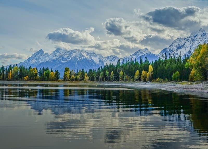 Sikt av Jackson Lake i den storslagna Teton nationalparken med reflexionen av träden på sjön och bergskedjan i backgen arkivfoton