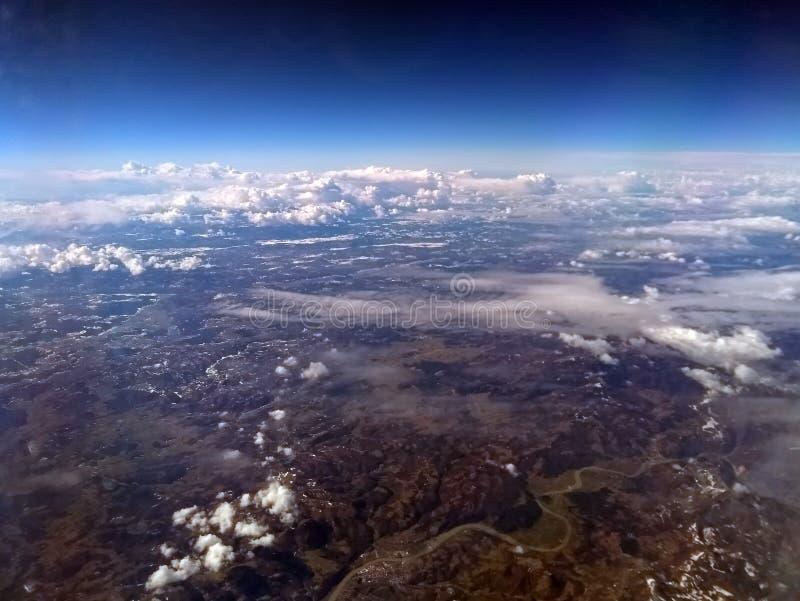 Sikt av jord från ett flygplan med europeiskt berglandskap med floder och snö med spridda vitmoln och mörker - blå himmel fotografering för bildbyråer