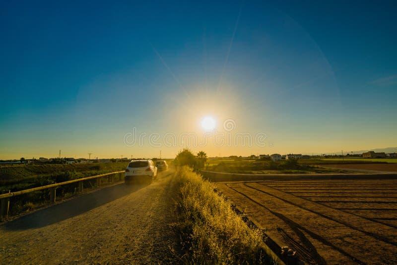Sikt av jordbruks- fält och byggnader nära Valencia för solnedgång spain arkivfoto