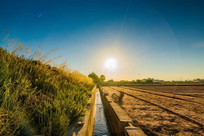 Sikt av jordbruks- fält och byggnader nära Valencia för solnedgång spain arkivbild