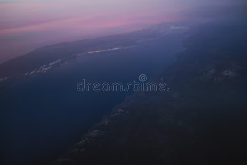 Sikt av jorden och Laket Baikal från fönstret av ett flygplan från en höjd av 10 000 meter royaltyfri bild