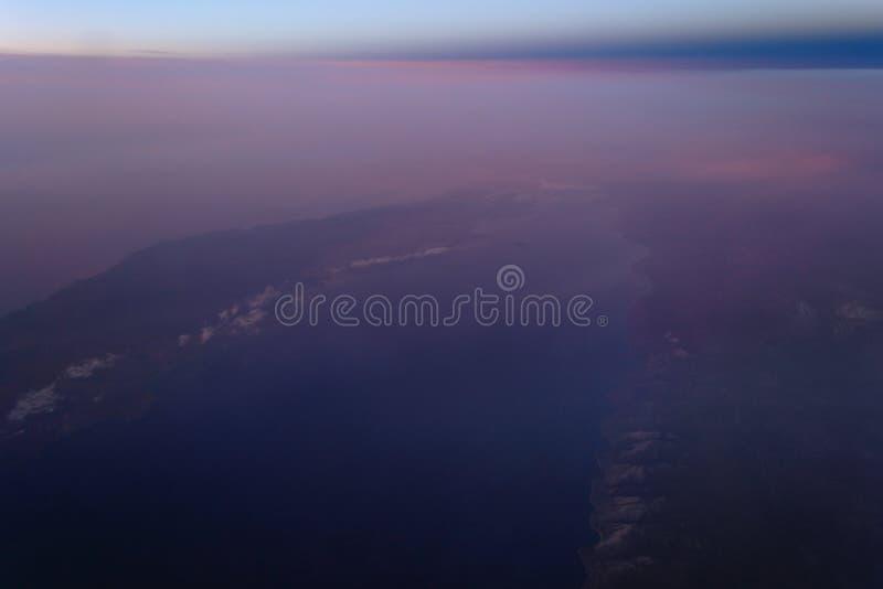 Sikt av jorden och Laket Baikal från fönstret av ett flygplan från en höjd av 10 000 meter arkivbilder