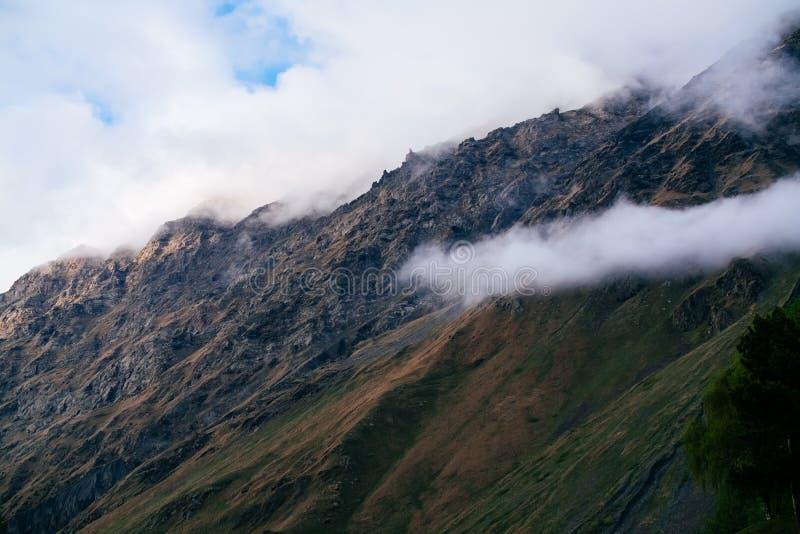 Sikt av Kaukasus berg nära Kazbegi, Georgia på en dimmig dag arkivfoto