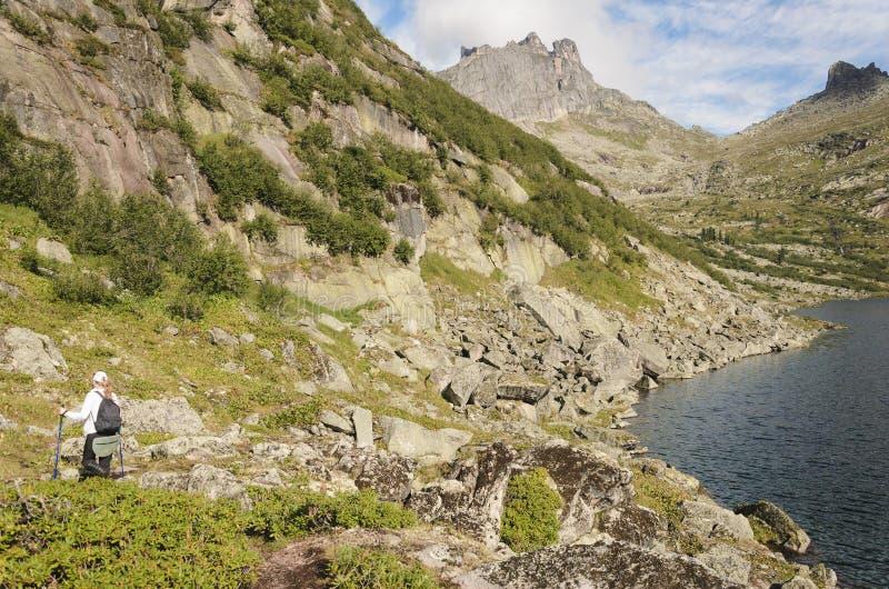 Sikt av klipporna, skogen och turisten med en stor ryggsäck, Ergaki berg arkivbilder
