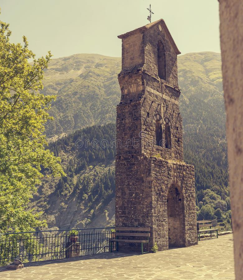 Sikt av klockatornet i en traditionell grekisk by Melissourgoi Epirus, Grekland i bergnärbilden arkivfoton