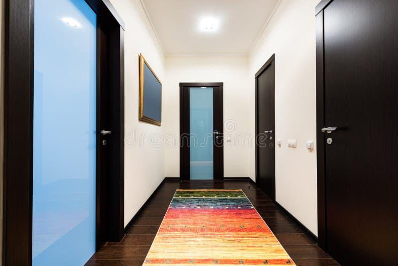 sikt av korridoren med trädörrar i lägenhet royaltyfri fotografi