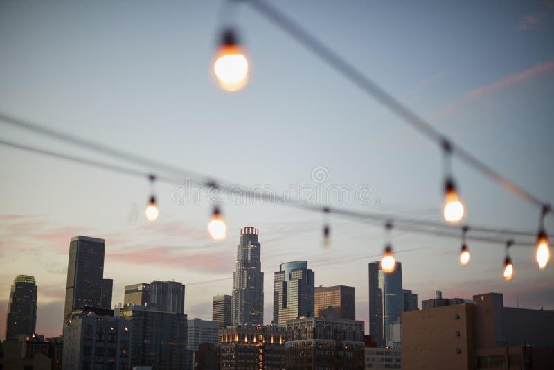 Sikt av Los Angeles horisont på solnedgången med rad av ljus i förgrund royaltyfria foton
