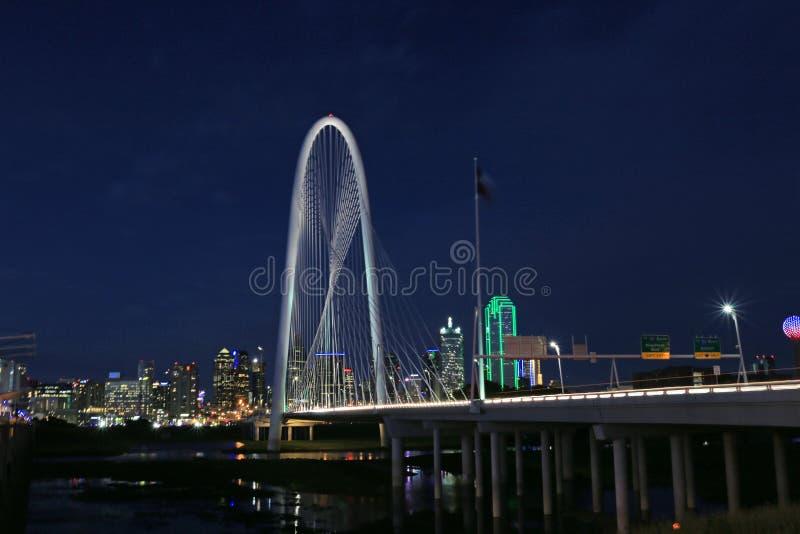Sikt av Margaret Hunt Bridge med Dallas Skyline i bakgrunden på natten royaltyfria bilder