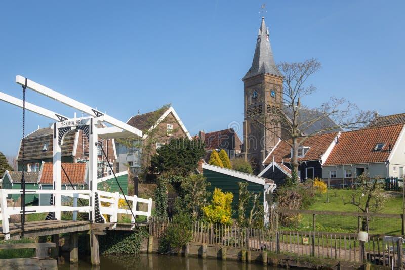 Sikt av maximumen klaffbro, trähus och kyrkligt torn för protestant i byn av Marken, Nederländerna royaltyfria foton
