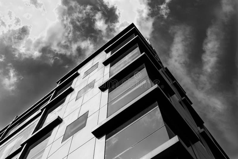 Sikt av min kontorsbyggnad underifrån med bakgrund för molnig himmel Svartvit bild royaltyfri foto