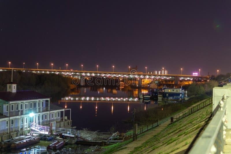 Sikt av nattstaden på flodbanken Sikt av tunnelbanabron i Nizhny Novgorod Reflexion av träd i floden Oka royaltyfri fotografi
