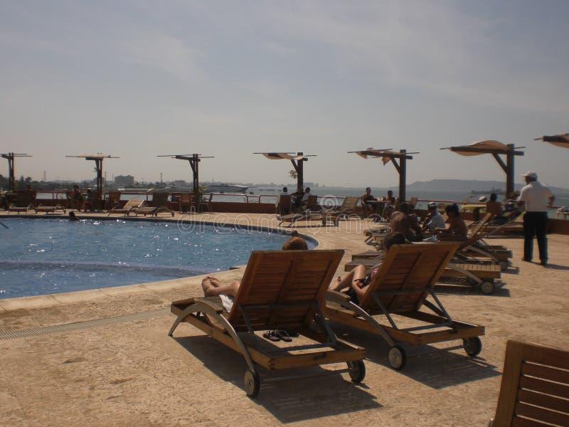 Sikt av pölen och sunbeds omkring med badare som solbadar i hotellet av det karibiskt royaltyfri fotografi