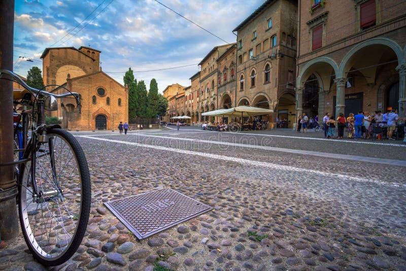 Sikt av piazza Santo Stefano på aftonen med folk och en cykel, Bologna, Italien arkivbilder