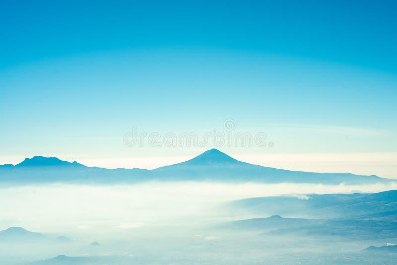 Sikt av popocatepetl som är inflight med sommarkänsla för blå himmel royaltyfri bild