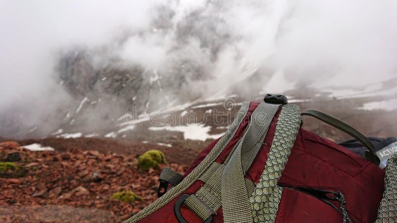 Sikt av remryggsäcken i bergen Moln driver förgången snö är synliga på berglutningarna royaltyfria bilder