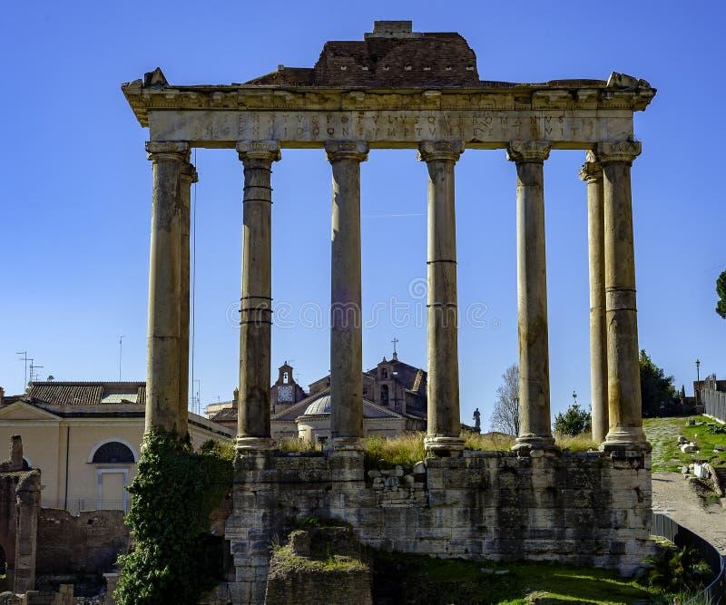Sikt av Roman Forum, fokus på templet för Saturn ` s i förgrund royaltyfri foto