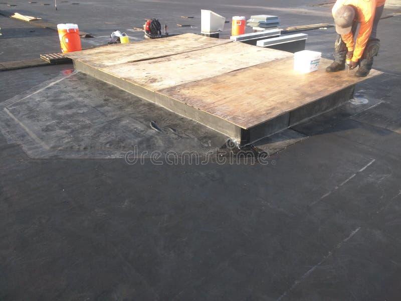 Sikt av Rooferdanande som taklägger reparationer; Ac-trottoarkant på det plana taket för reklamfilm EPDM royaltyfri bild