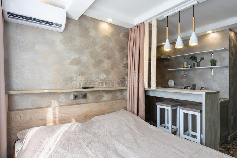 Sikt av sängen, stången och köket i ett litet hotellrum royaltyfria foton