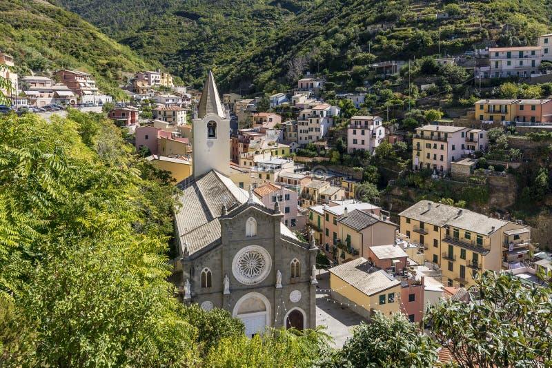 Sikt av sjösidabyn av Riomaggiore och kyrkan av San Giovanni Battista, Cinque Terre, Liguria, Italien arkivbild