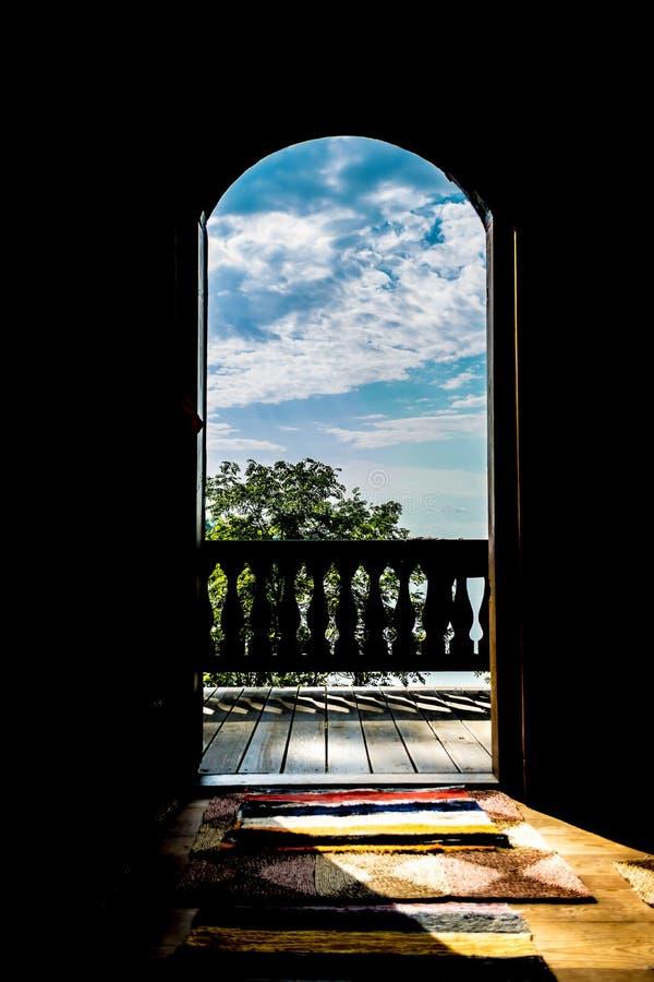 Sikt av skoglandskapet med en sjö på en klar solig dag till och med den öppna dörren av ett hus med en forntida terrass royaltyfria bilder