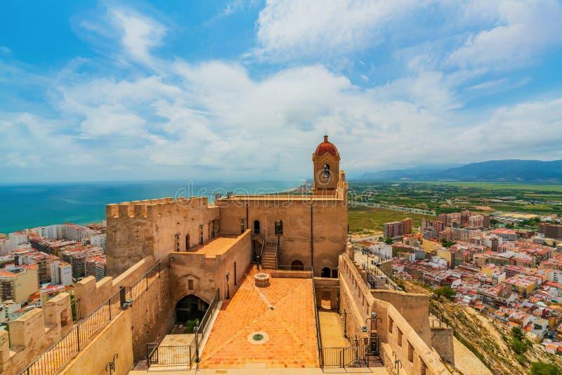 Sikt av slotten i staden av Cullera på en molnig dag Område av Valencia spain royaltyfri bild