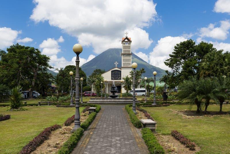 Sikt av staden av La Fortuna i Costa Rica med den Arenal vulkan på baksidan arkivbild