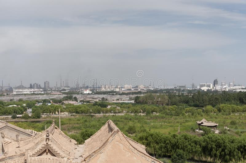 Sikt av staden av Jiayuguan med fabriker som sänder ut gaser till atmosfären, i det Gansu landskapet, Kina royaltyfri fotografi