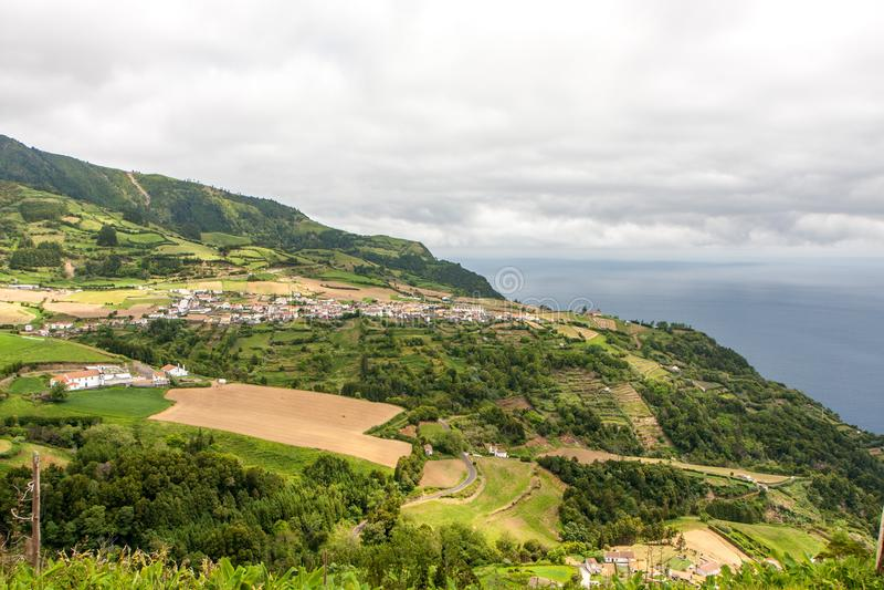Sikt av staden med lantgårdar i bergen nära havet royaltyfria bilder