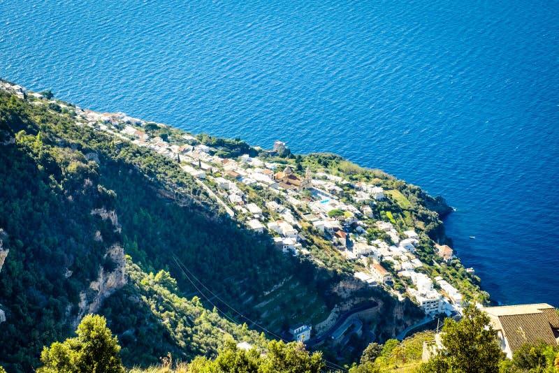 Sikt av staden av Vettica Maggiore på den berömda Amalfi kusten med golfen av Salerno i soligt ljus arkivbilder