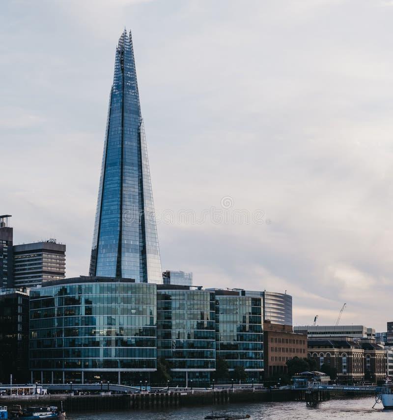 Sikt av stadshorisont och skärvan, London, UK, från den motsatta sidan av flodThemsen under blå timme royaltyfri foto