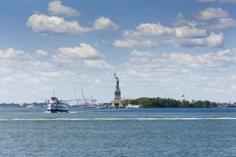 Sikt av statyn av frihet i New York City, med turist- fartyg i Hudson River royaltyfri foto