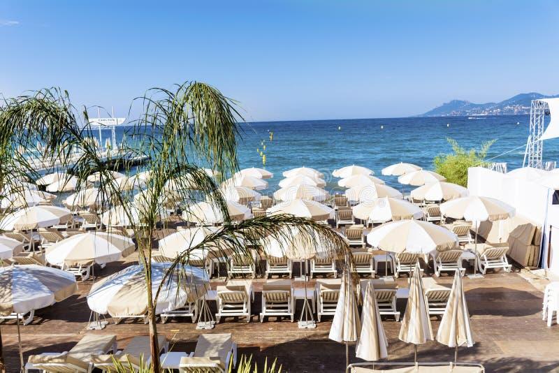 Sikt av stranden på cannes med stolar och slags solskydd på den vita sandiga stranden arkivbilder