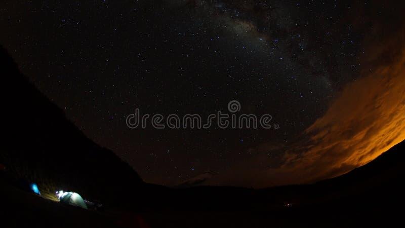 Sikt av tända tält på en stjärnklar natt med den Cotopaxi vulkan i bakgrunden royaltyfri fotografi