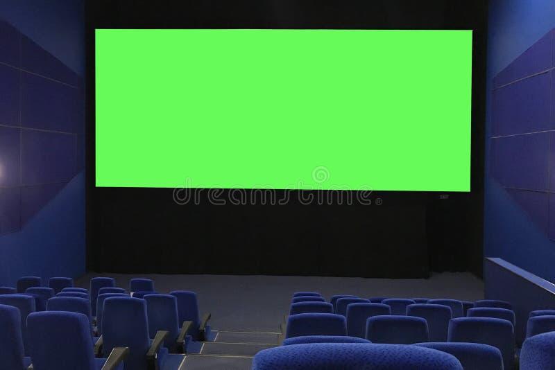 Sikt av tom de stora gröna för en skärm uppifrån raderna för biokorridor och Bio med rader av blåa stolar royaltyfri fotografi