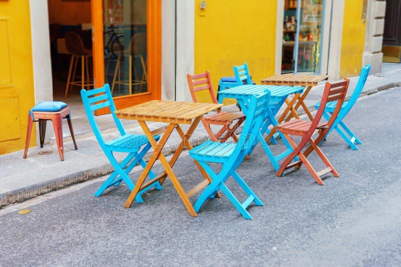 Sikt av tomma blåa och bruna tabeller i utomhus- kafé på gatan fotografering för bildbyråer