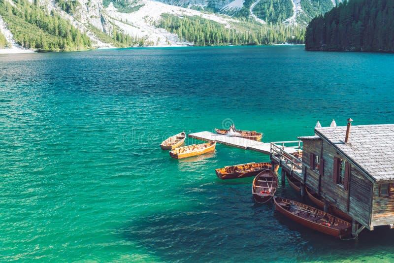 sikt av trähuset på vatten med pir- och fartygsjön i dolomitesberg royaltyfri foto