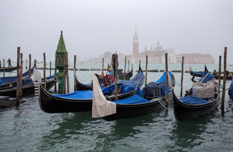 Sikt av traditionella gondoler på kanalen som är stor i Venedig Venezia i en dimmig dag med San Giorgio Island på bakgrunden, Ita royaltyfria bilder
