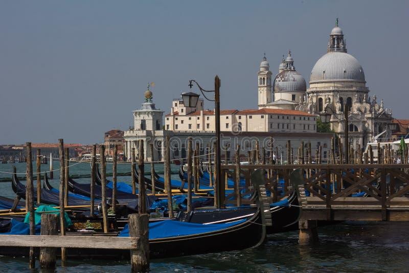 Sikt av traditionella gondoler på kanalen som är stor med historiska basilikadi Santa Maria della Salute royaltyfri fotografi
